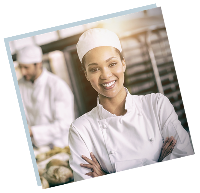A commercial baker smiles with bread and coworkers in the background